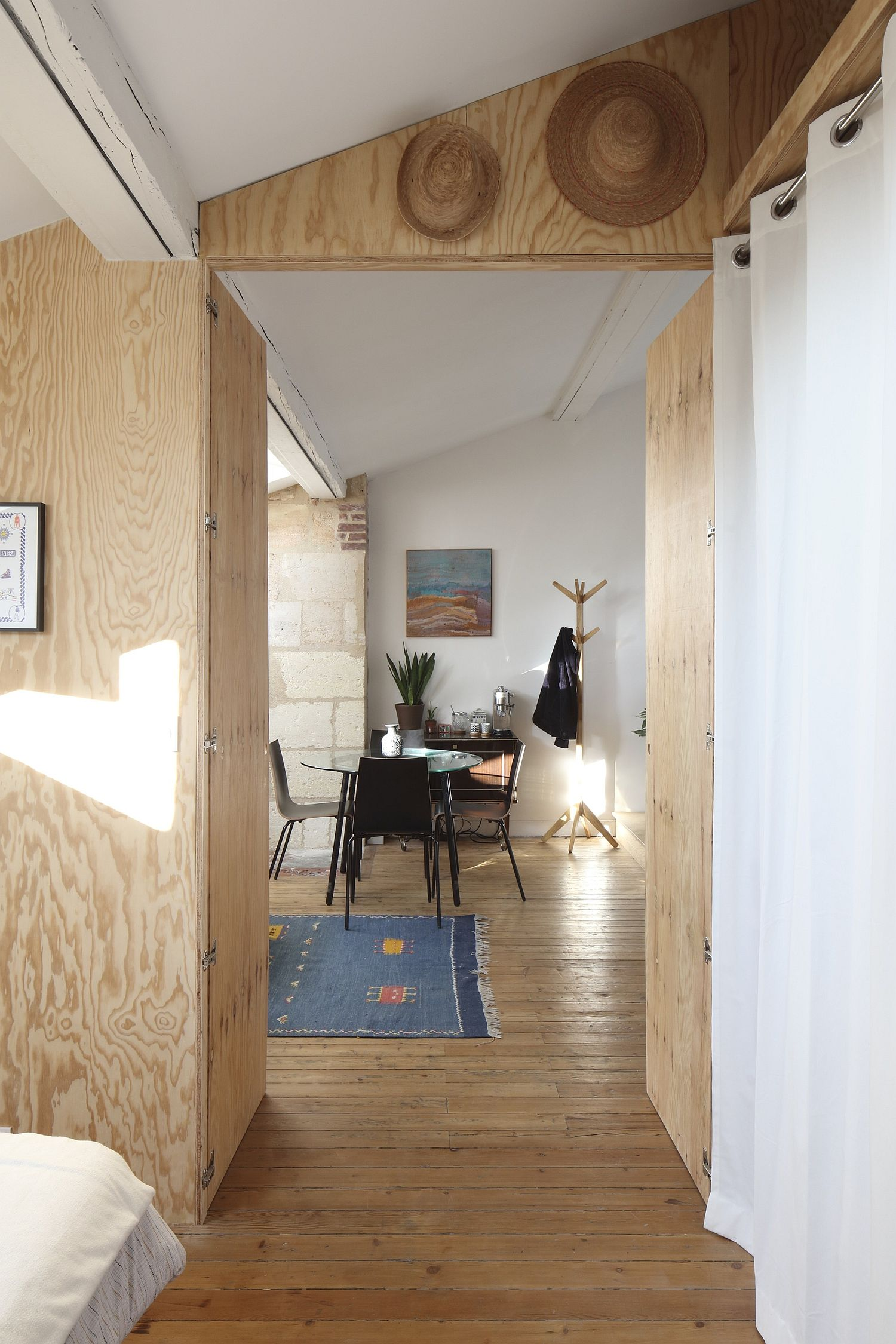 Unfinished wooden surfaces add a bit of rustic warmth to the modern apartment in white