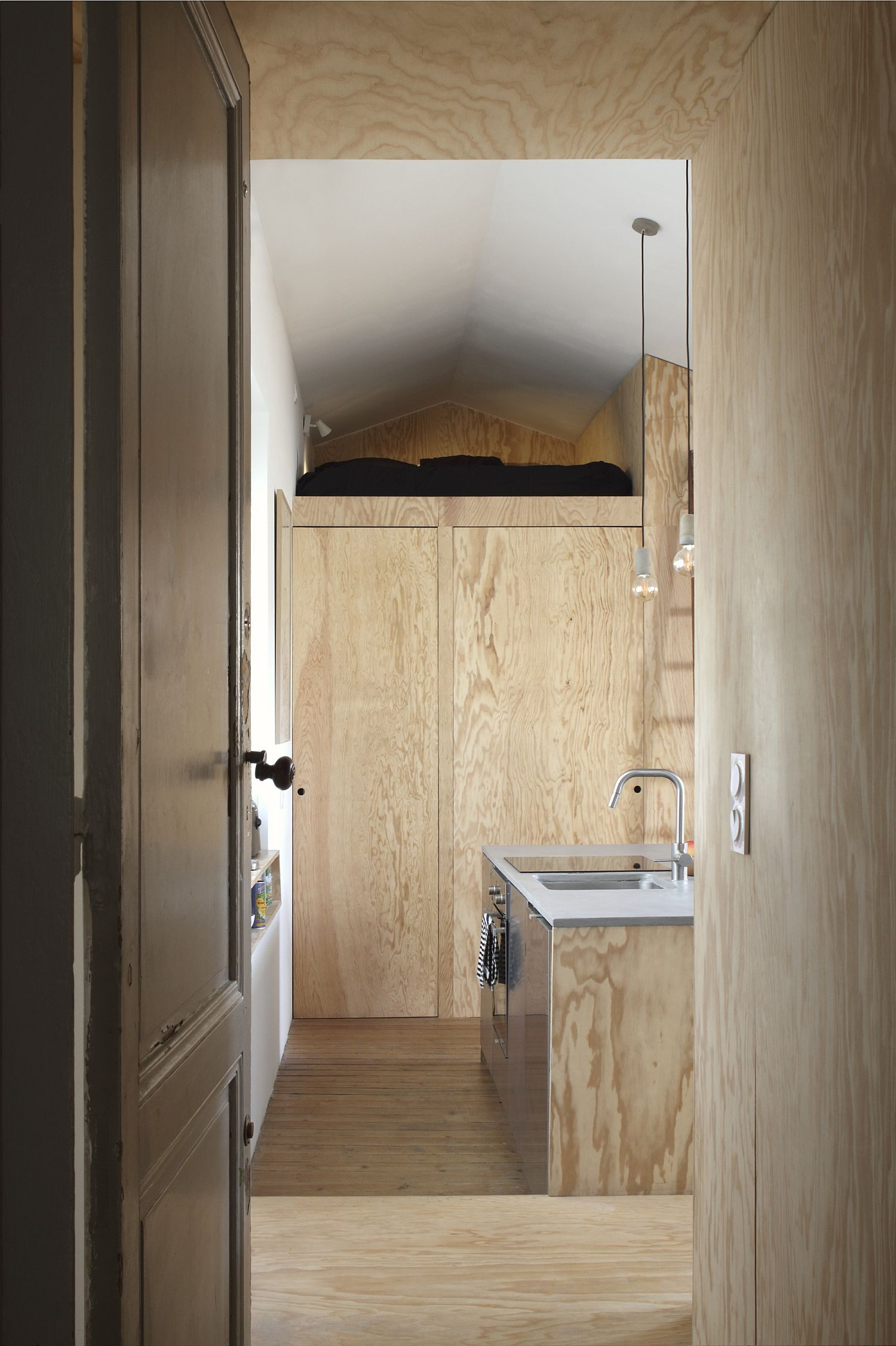Wooden walls and custom units create ample storage inside the apartment
