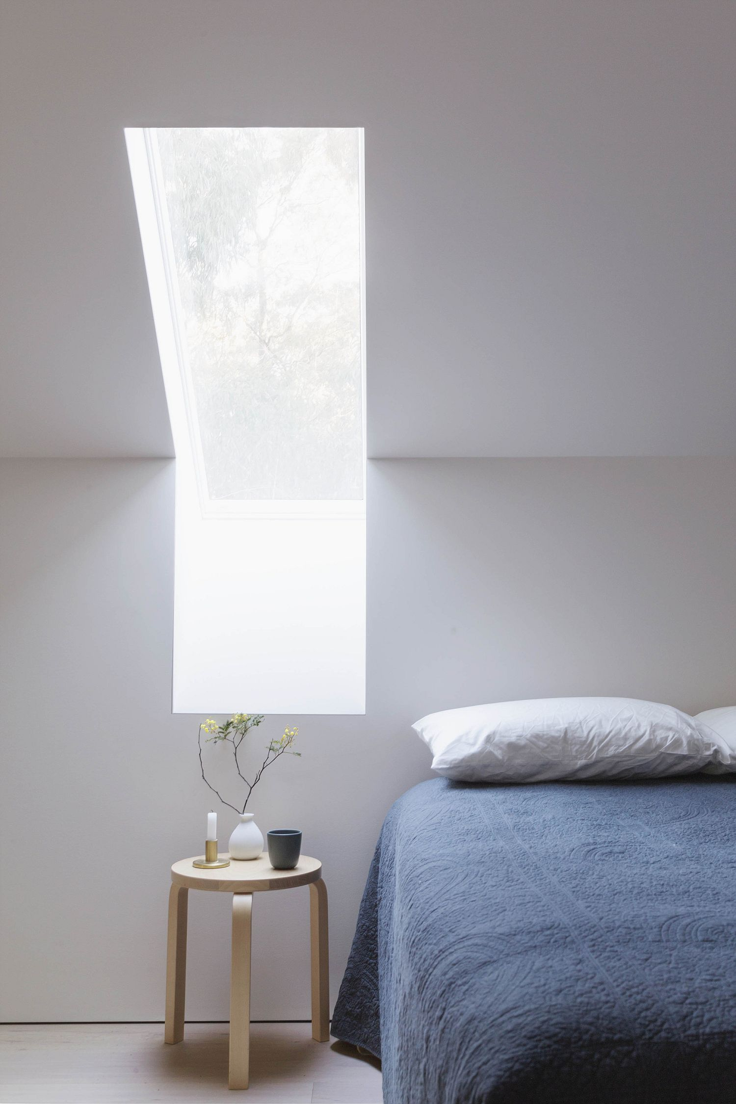 Clever use of windows brings natural light into the minimal bedroom