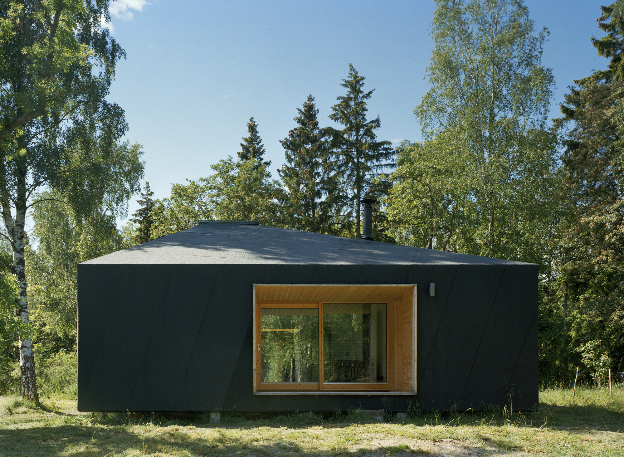 Dark exterior of the small summer house in woods allows it to blend in with the backdrop