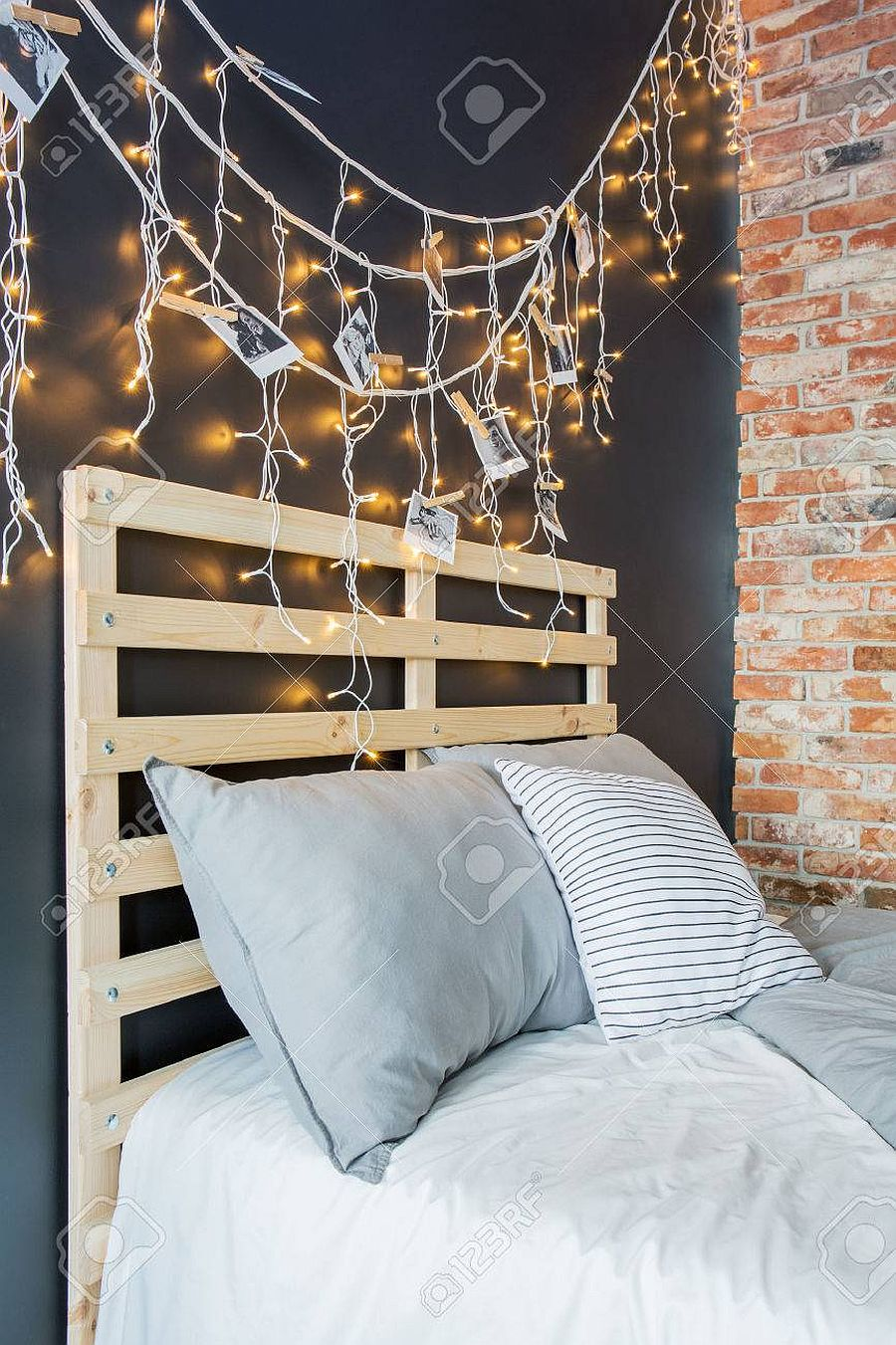 Eye-catching bedroom lighting and DIY pallet headboard make a big impression