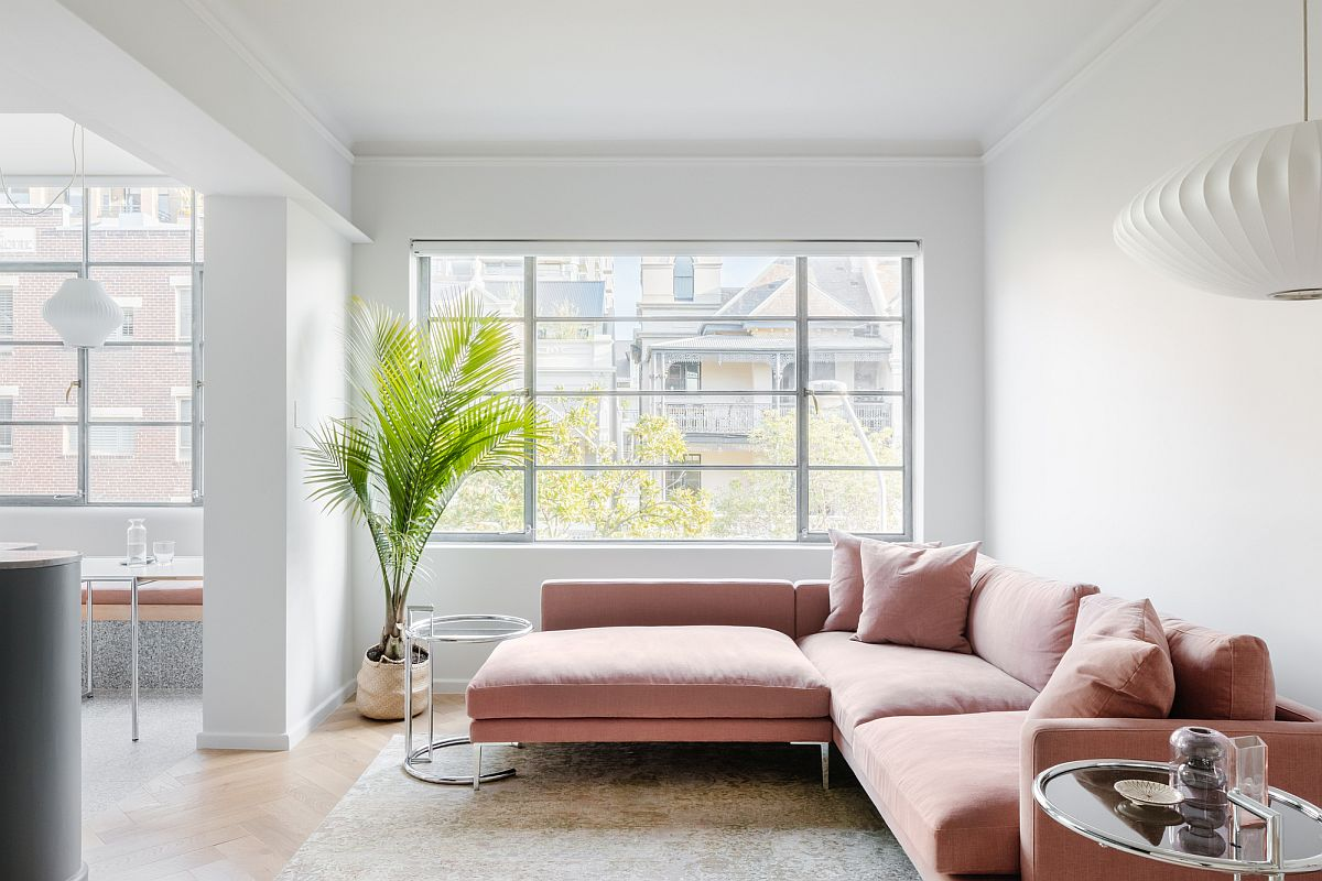 Fabulous sectional in pastel pink adds color to the white living room