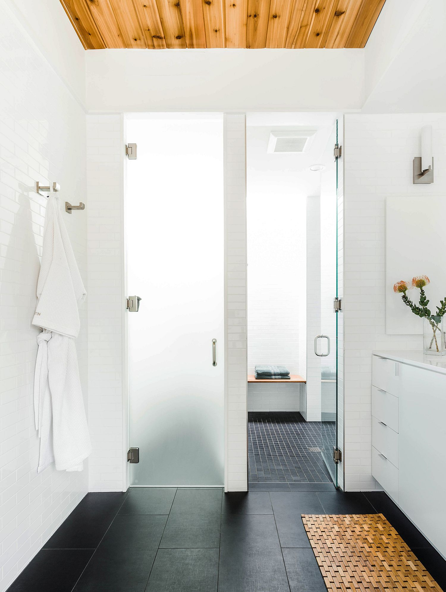 Gorgeous and relaxing bathroom in white with dark floor and wood ceiling