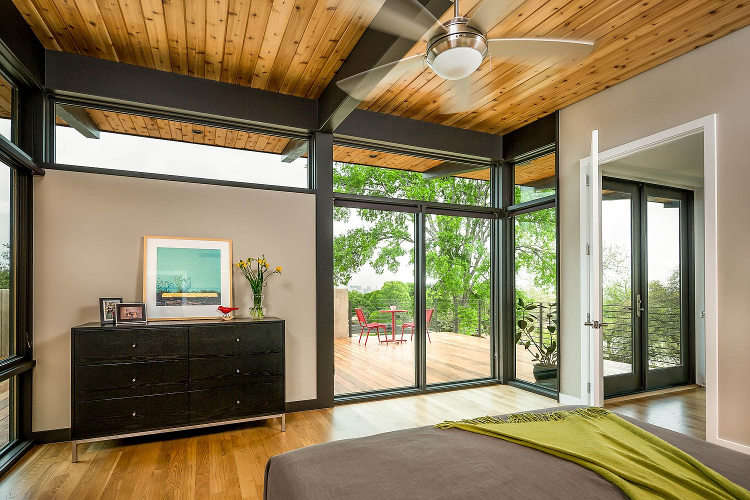 Metallic beams and wood create a cozy bedroom with many windows and glass walls