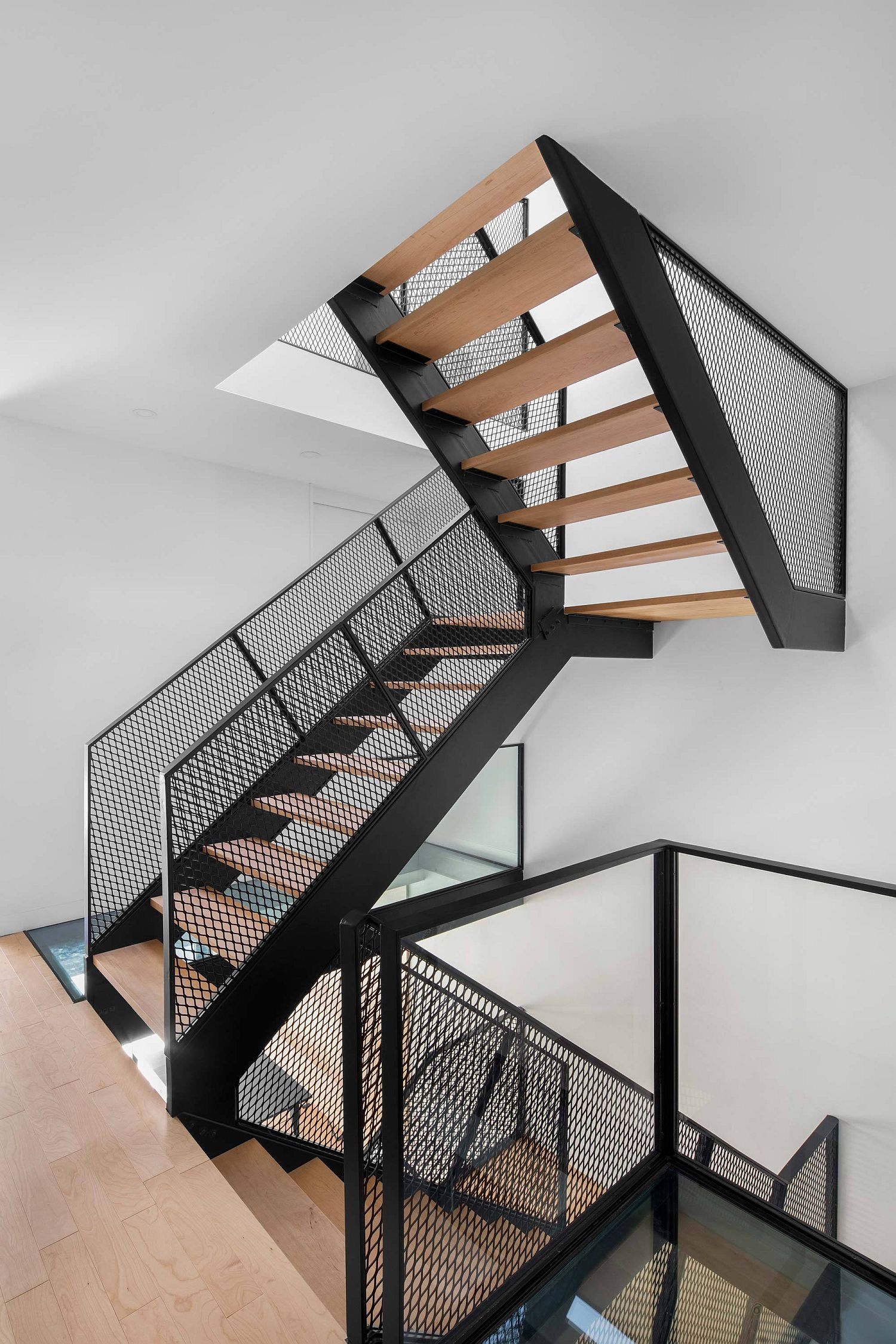 Metallic mesh and wood create a gorgeous central staircase in the house
