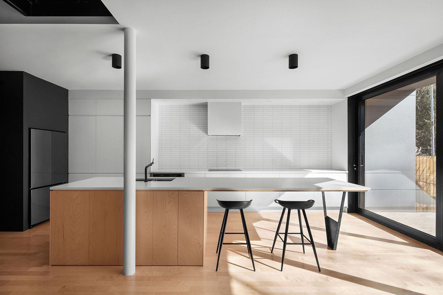 Minimal kitchen of the Montreal home in wood and white with black that anchors it