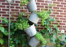 Tipsy-garden-feature-using-old-watering-cans-217x155