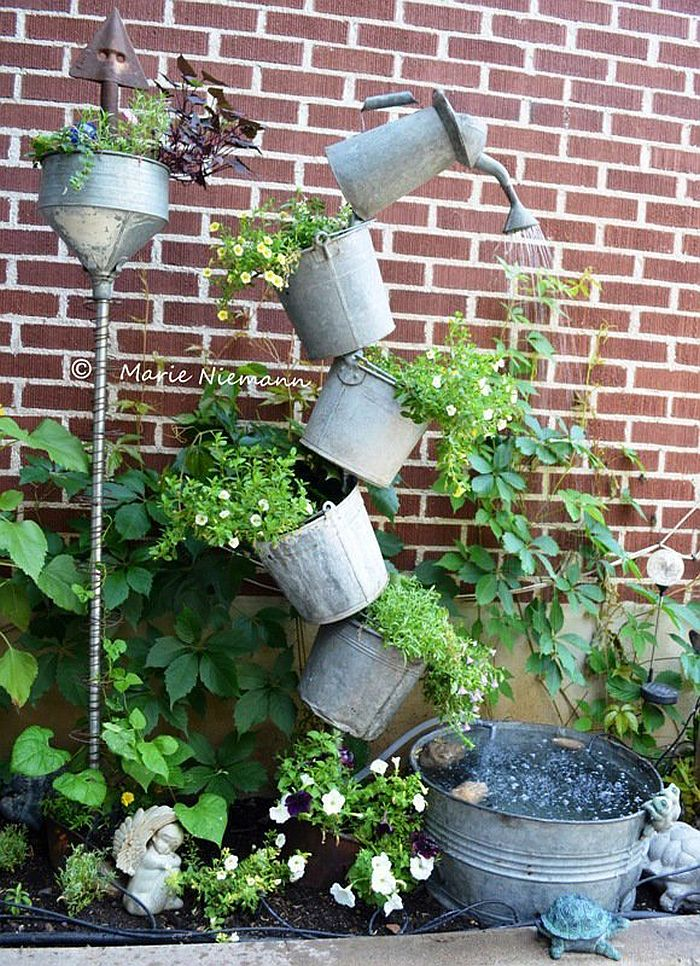 Tipsy garden feature using old watering cans