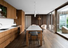 Wood-and-white-kitchen-with-sliding-glass-door-connecting-it-to-the-deck-outside-217x155