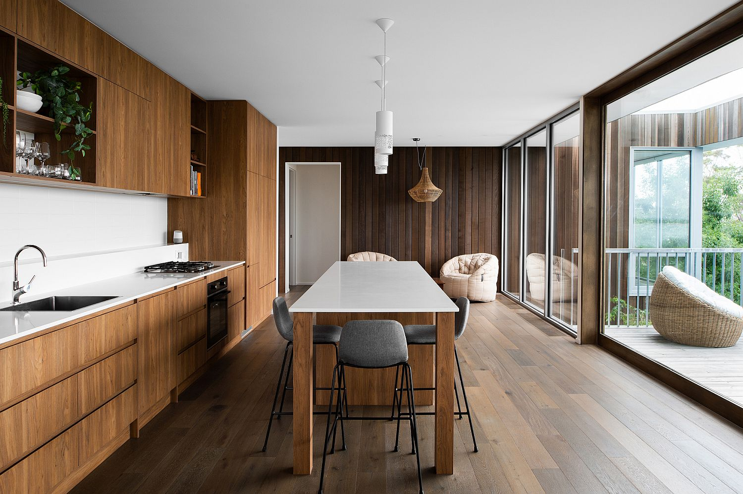 Wood-and-white-kitchen-with-sliding-glass-door-connecting-it-to-the-deck-outside