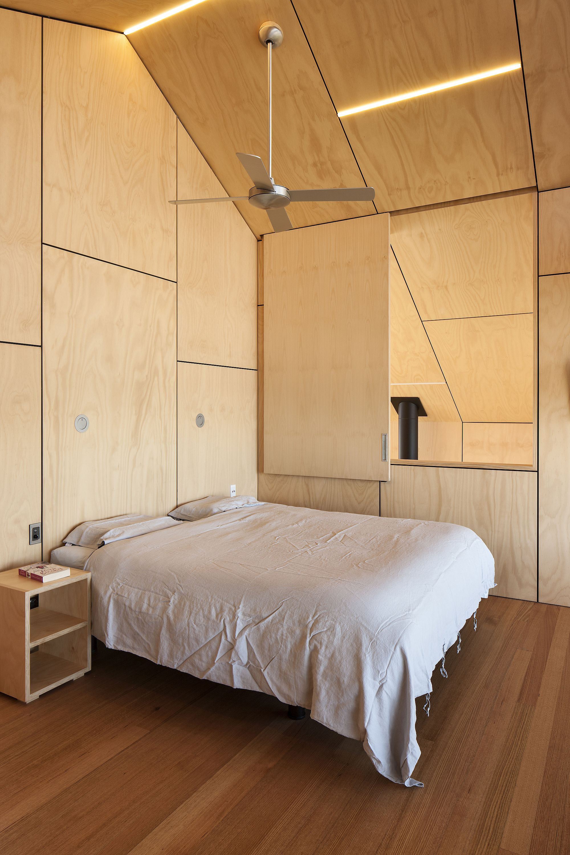 Bedroom feels much more cozier thanks to the wooden panels on walls