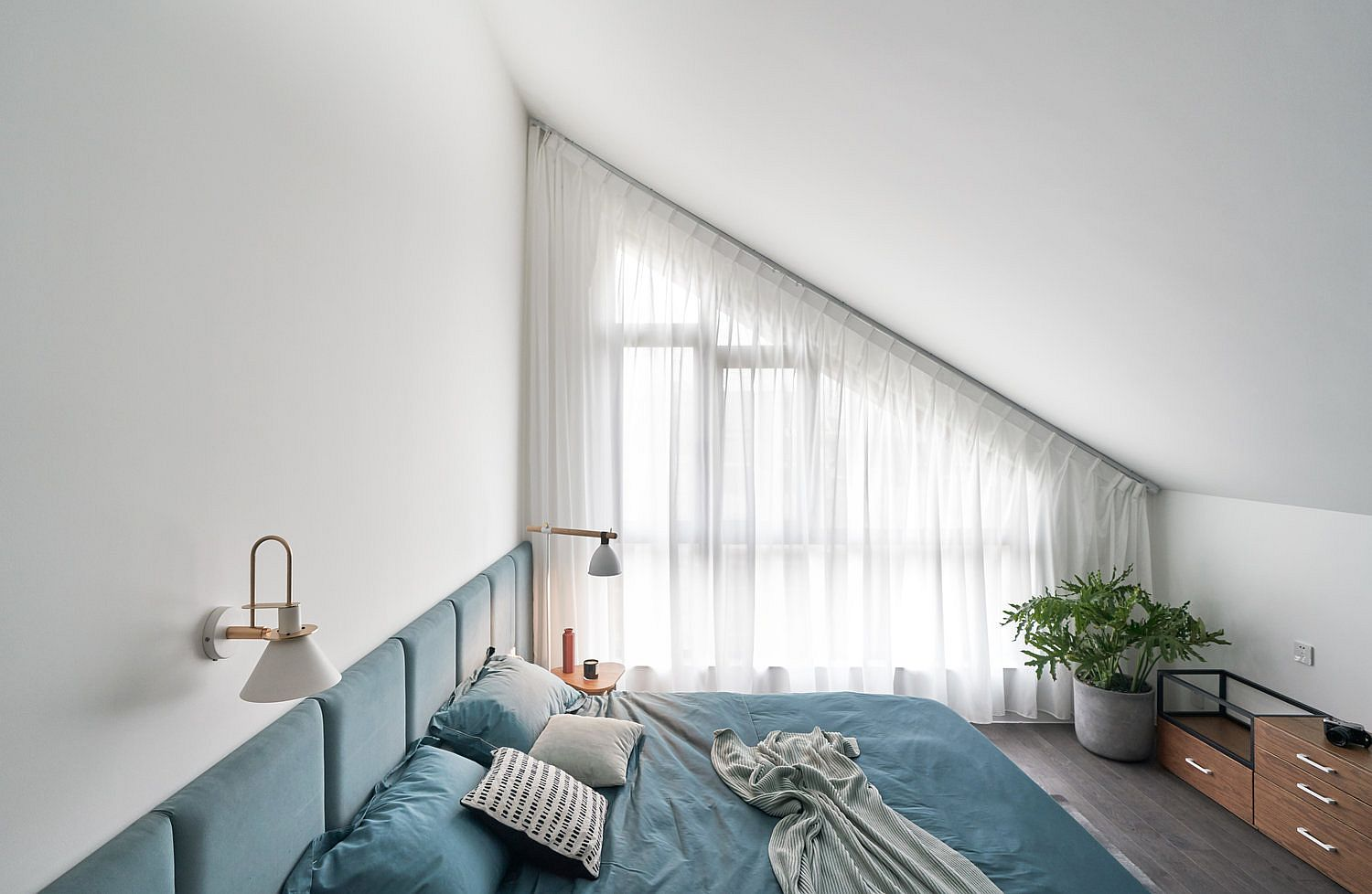Blues-and-greens-add-brightness-to-the-bedroom-in-white-with-slanted-ceiling