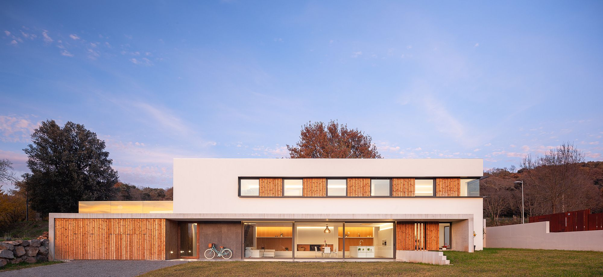 Box-like design of contemporary home in wood and white with lovely lighting