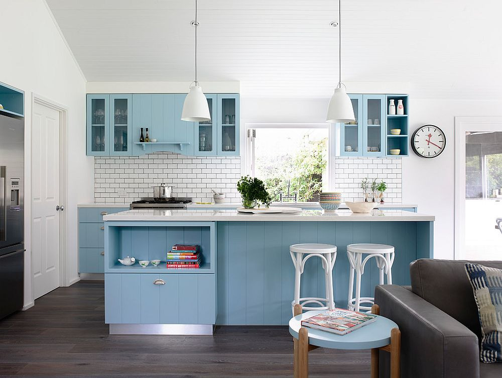 Cabinets and island bring a gentle shade of blue to the white kitchen