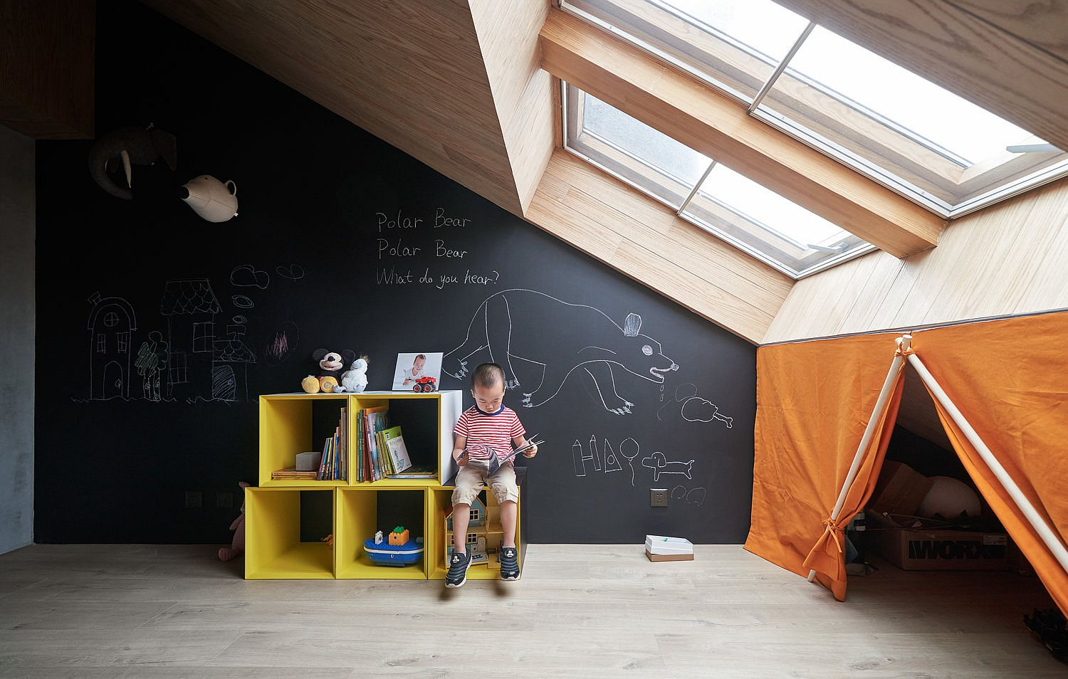 Ceiling windows bring ample light in to the kids' playroom with chalkboard wall