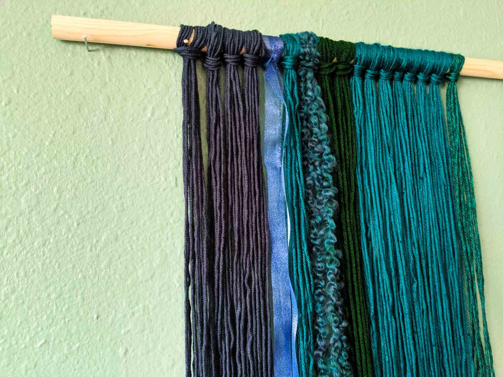 Continue adding yarn to the wall hanging