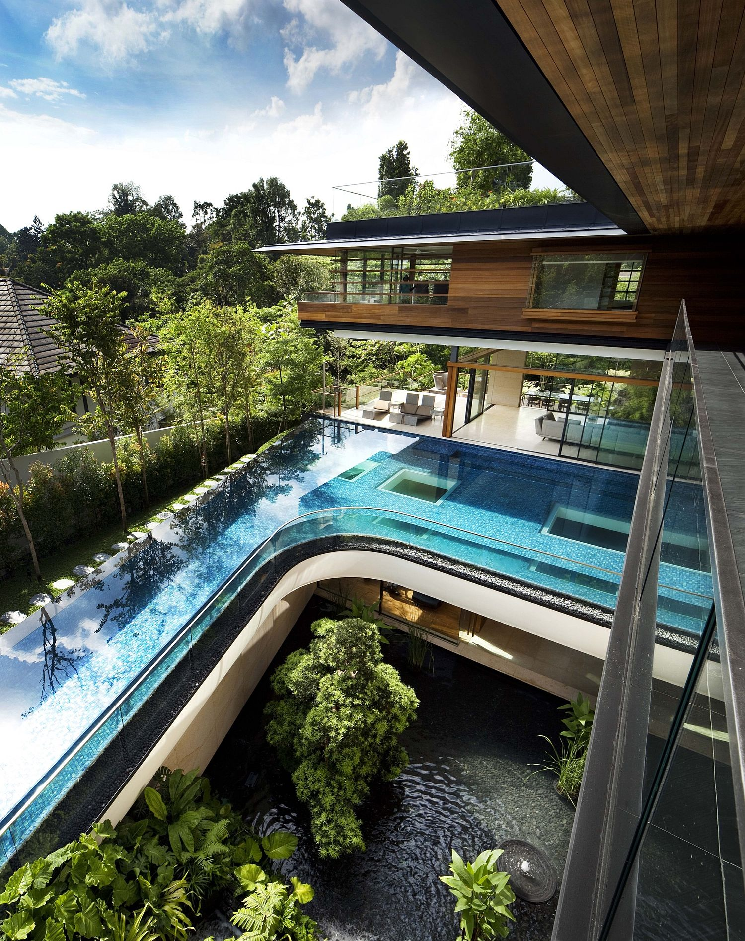 Curved swimming pool on the upper level with garden below