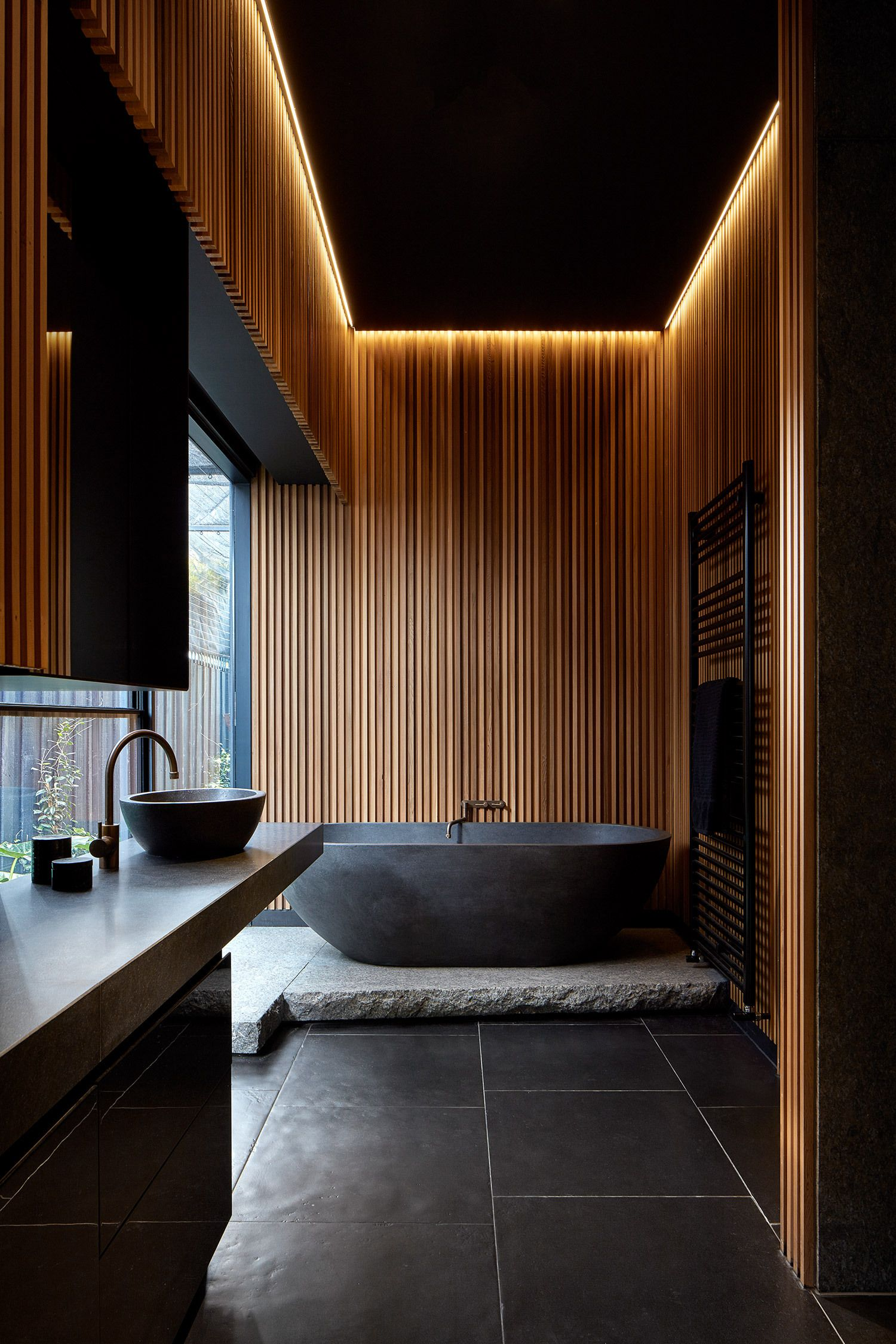Dark-wood-and-natural-stone-elements-give-the-bathroom-a-stunning-visual-appeal