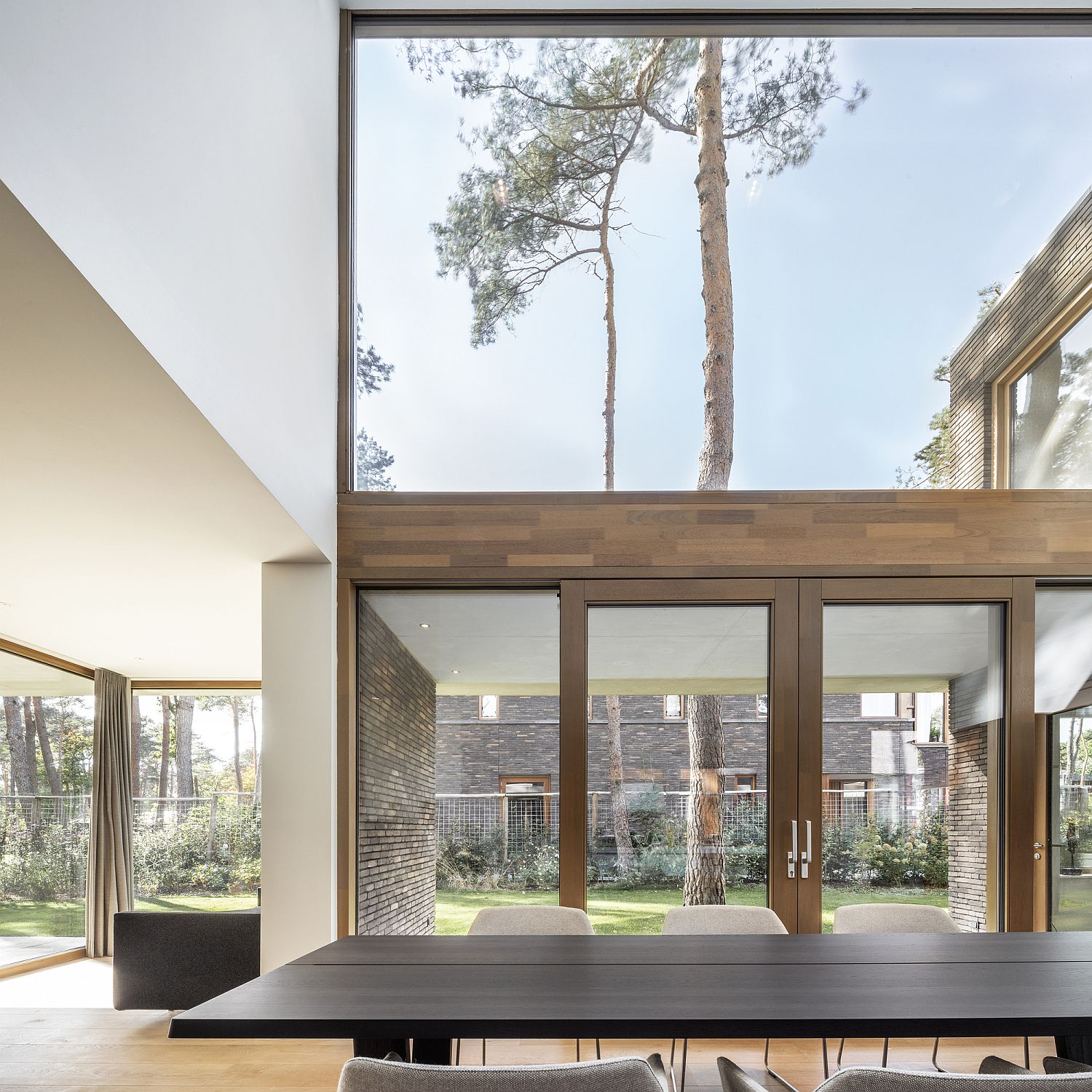 Floor-to-ceiling glass windows and timber frames make a bold statement
