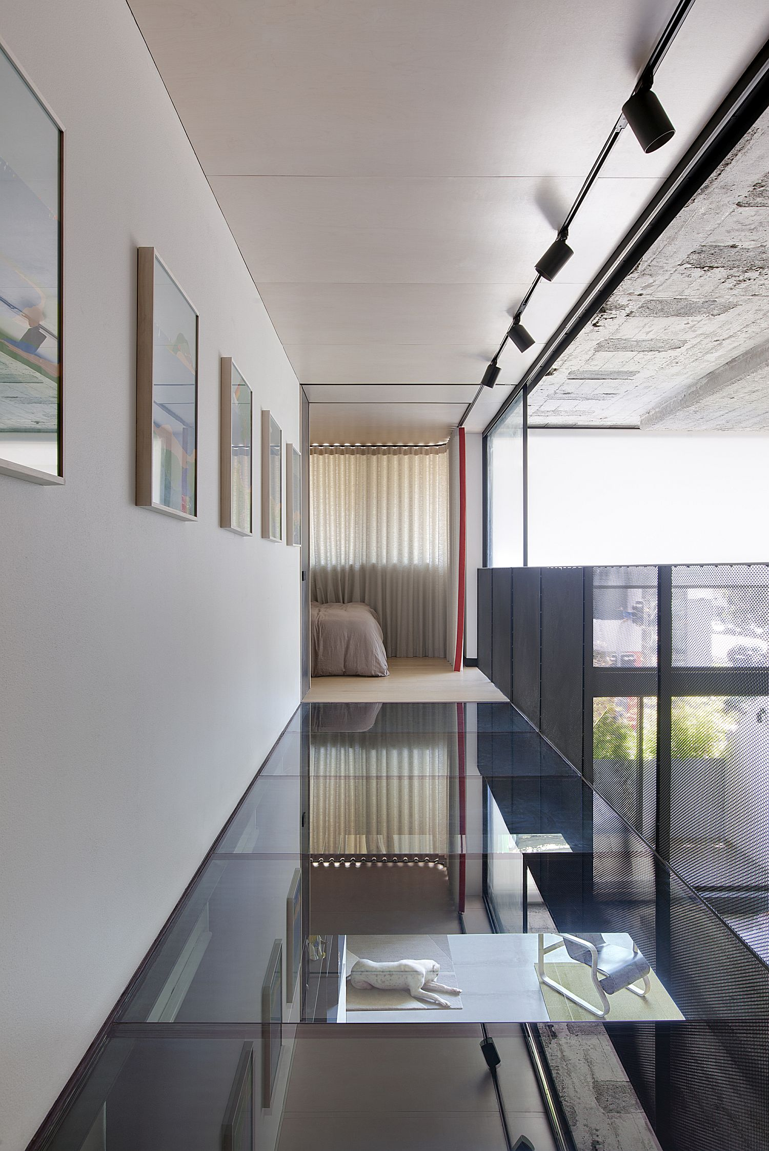 Glass walkway connects the two different upper levels of the house