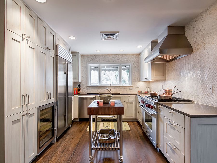 Glittering penny-tiled backdrop and narrow island on wheels for the small kitchen