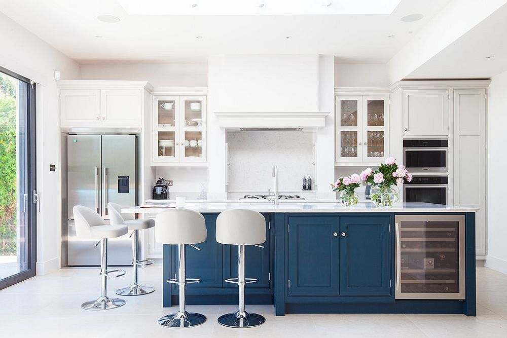Island adds a bold splash of navy blue to the brightly lit white kitchen