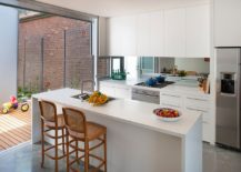 It-is-hard-to-miss-the-class-mirror-backsplash-in-this-small-contemporary-kitchen-217x155