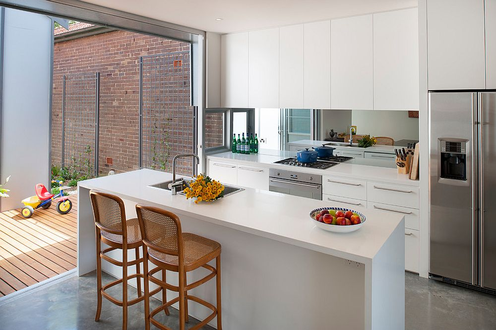 It is hard to miss the class mirror backsplash in this small contemporary kitchen