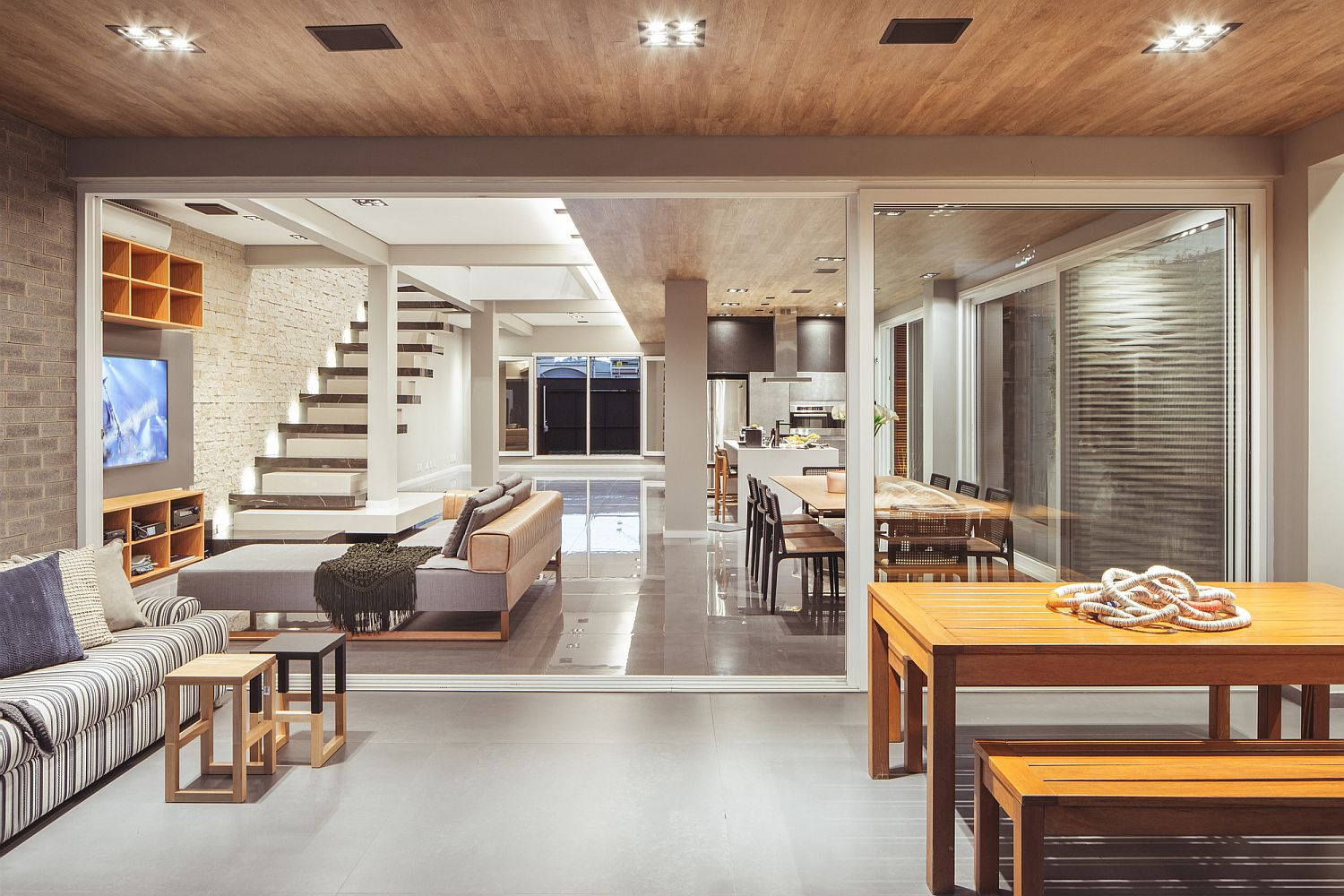 Large sliding glass doors connect the interior with the deck outside