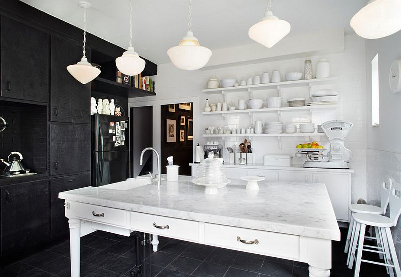 Marble kitchen countertops and black cabinets stand in contrast in the kitchen