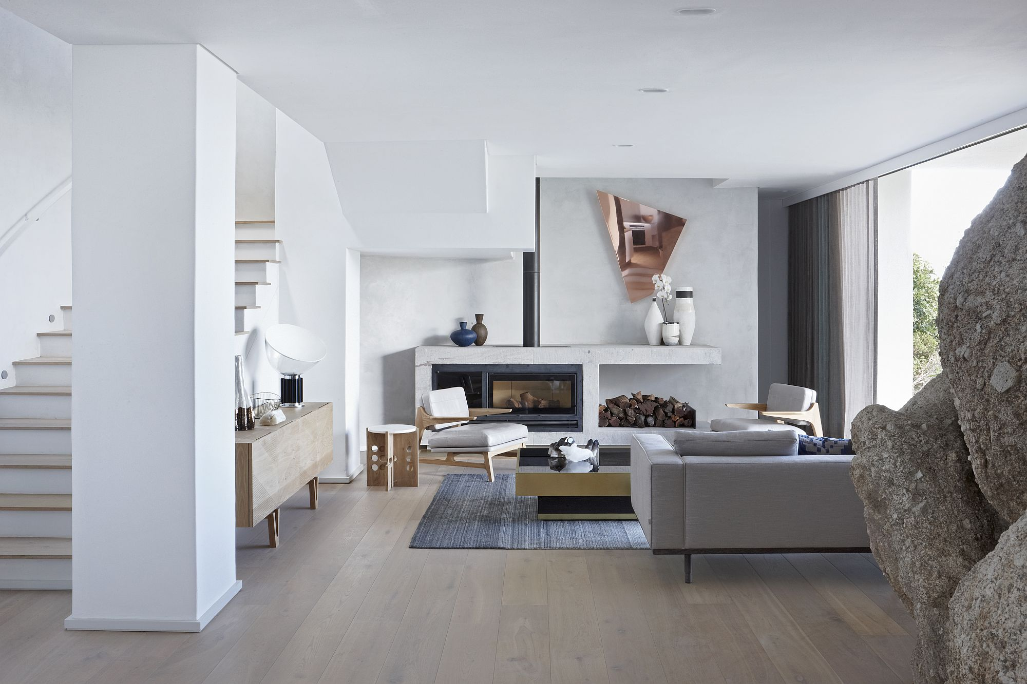 Minimal living room in white with a giant boulder that is a part of the interior