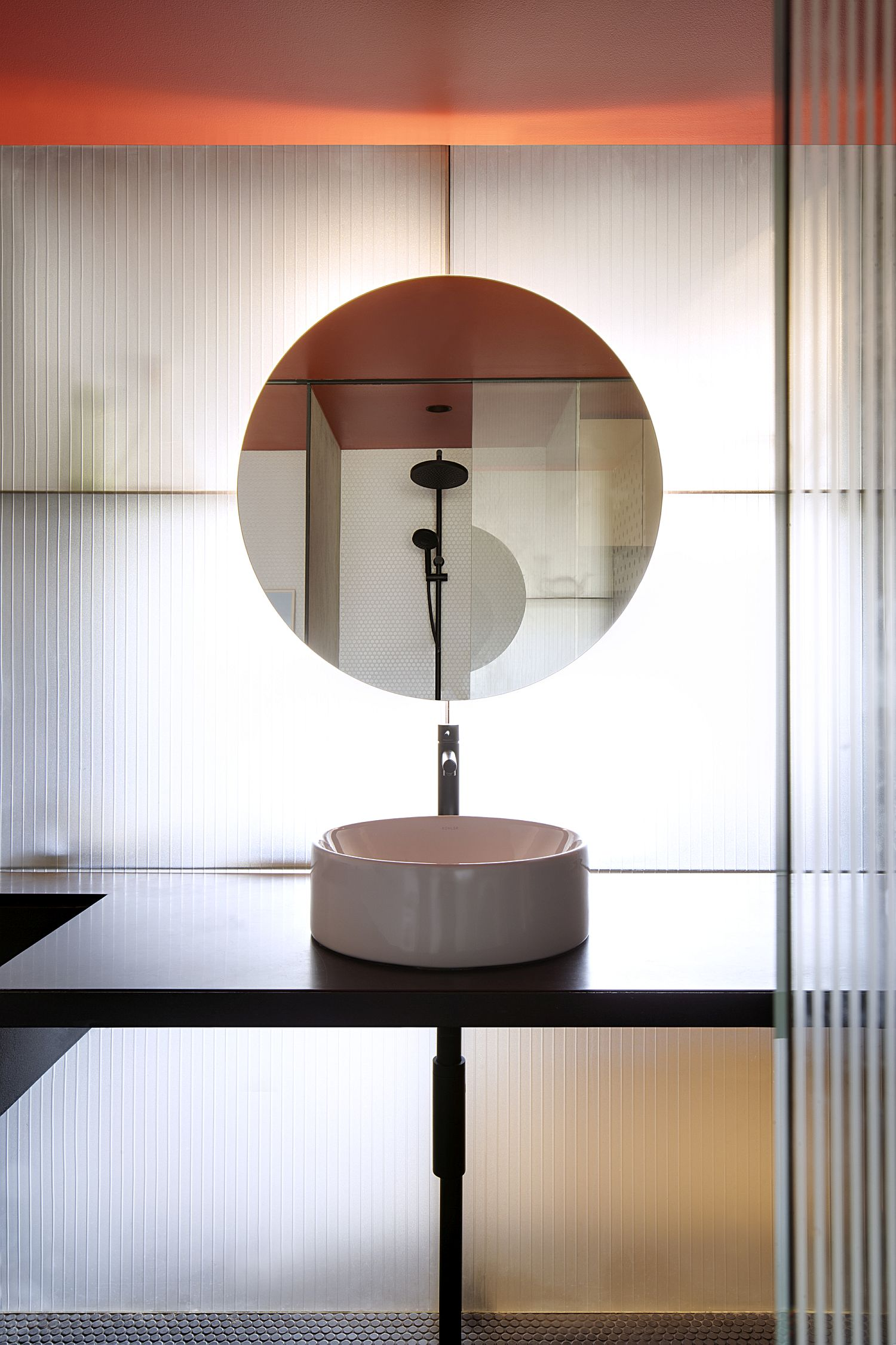 Minimal powder room with lovely round mirror and fab back light