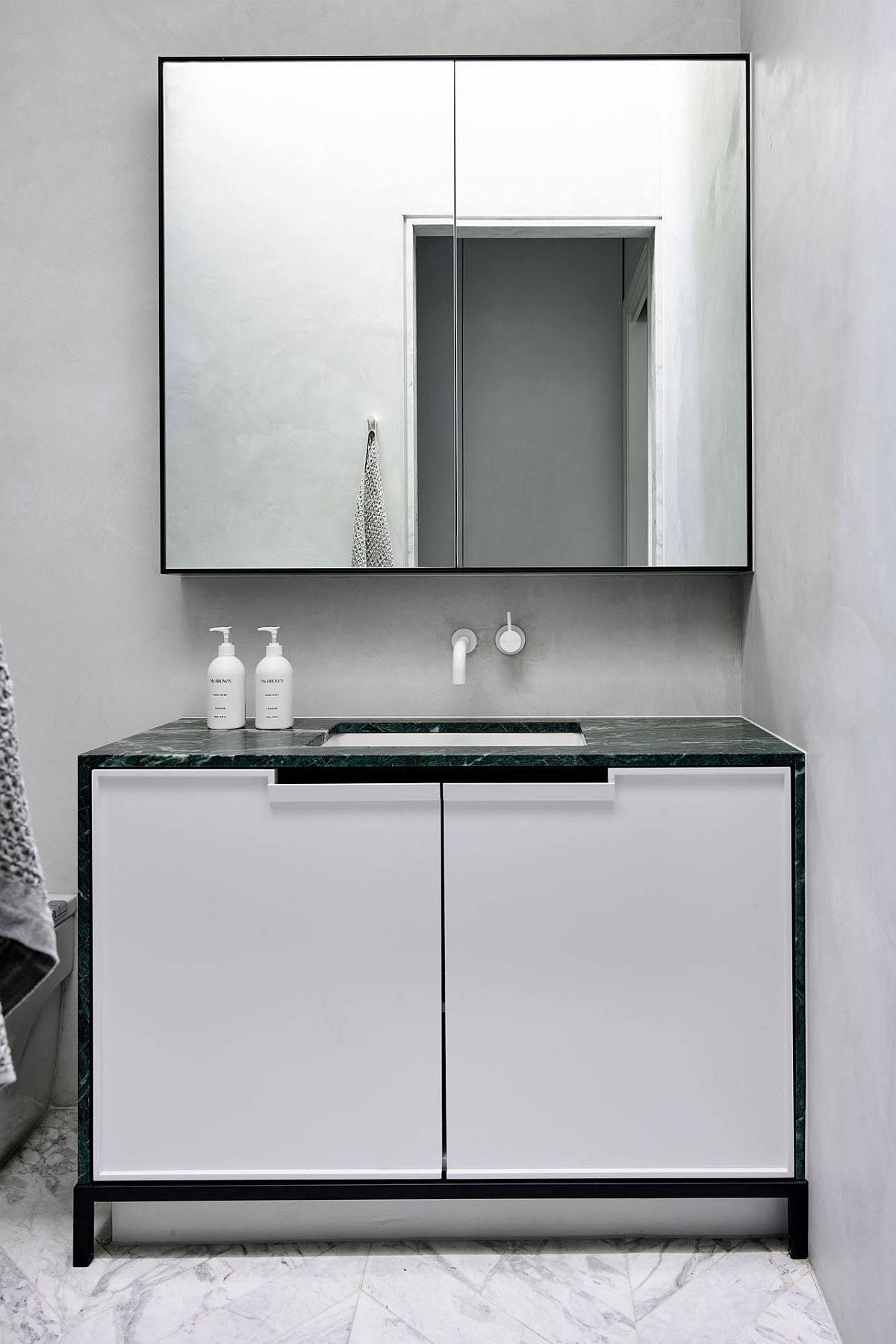 Modern minimal bathroom in white with a slim vanity and stone contertop
