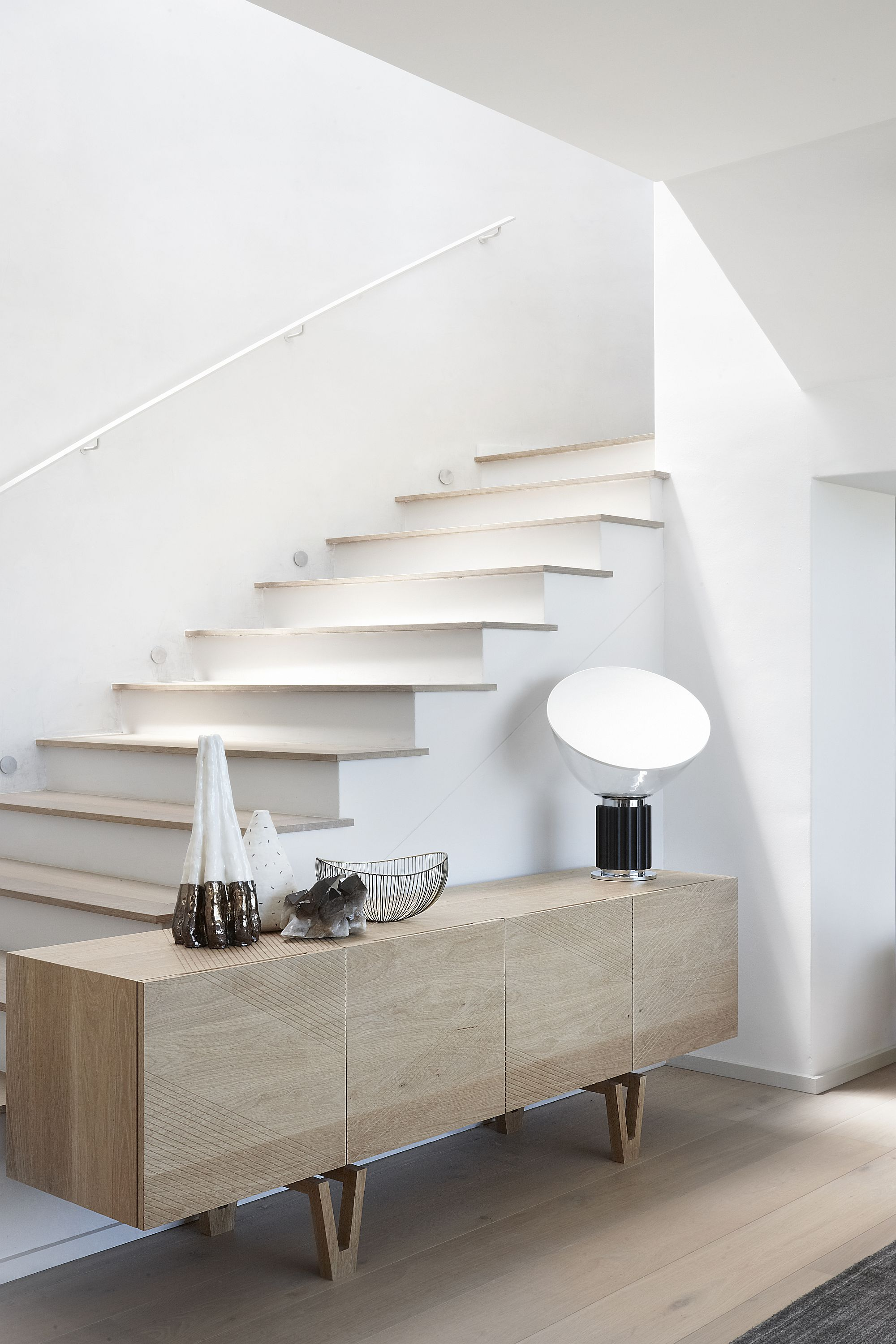 Side table next to the staircase has multiple storage and display options