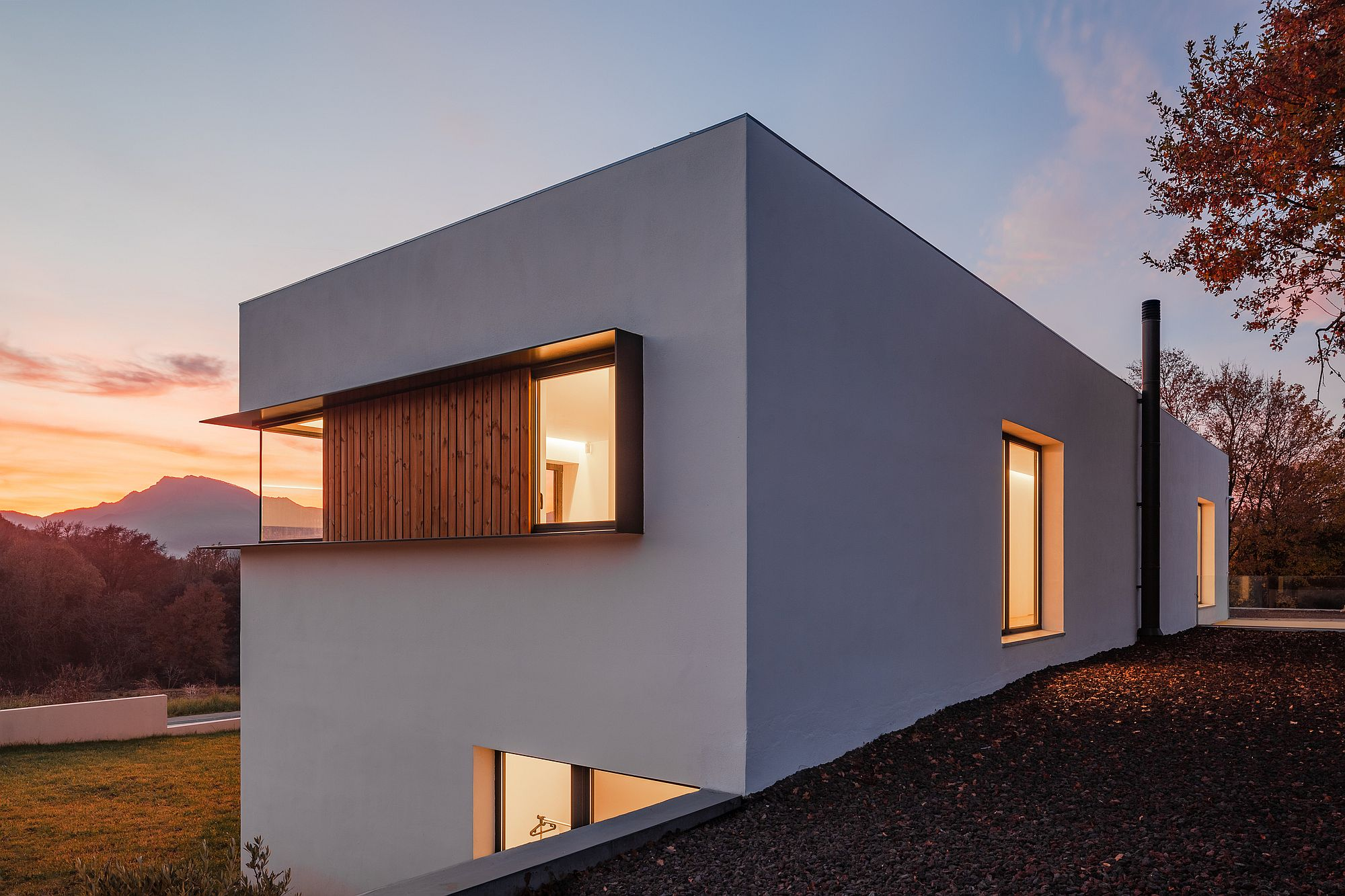 Sloped lot with contemporary home in white that has a private street facade