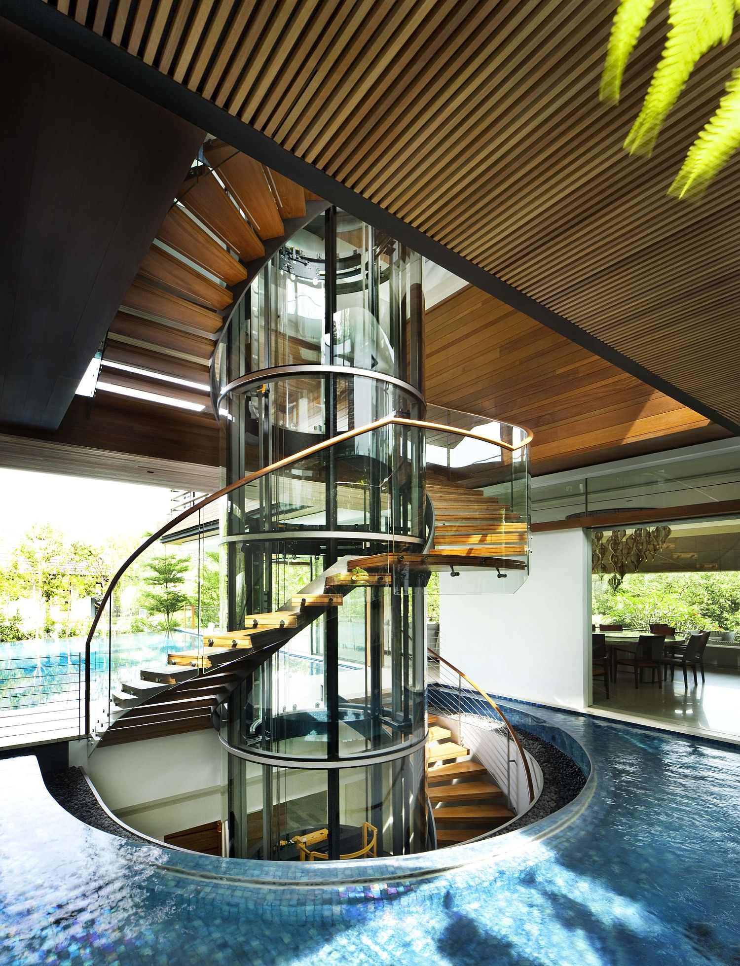 Spiral staircase connects various levels of the house even as the pool around it makes a statement