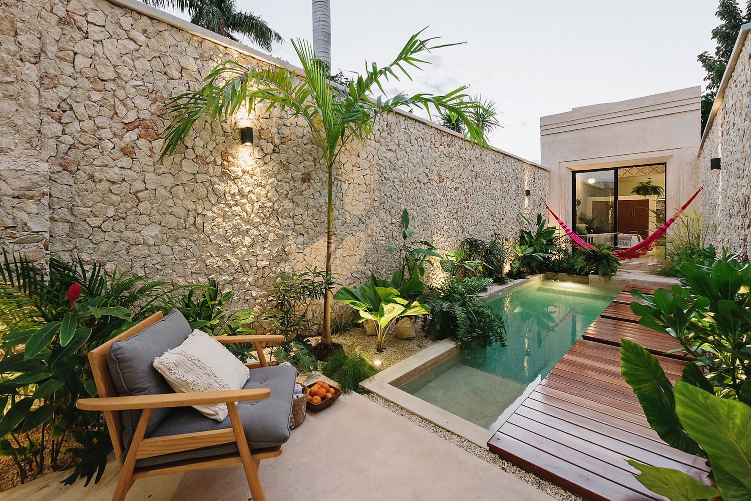 Stone-wall-lush-green-vegetation-and-a-slim-wooden-deck-create-a-private-and-relaxing-pool-zone