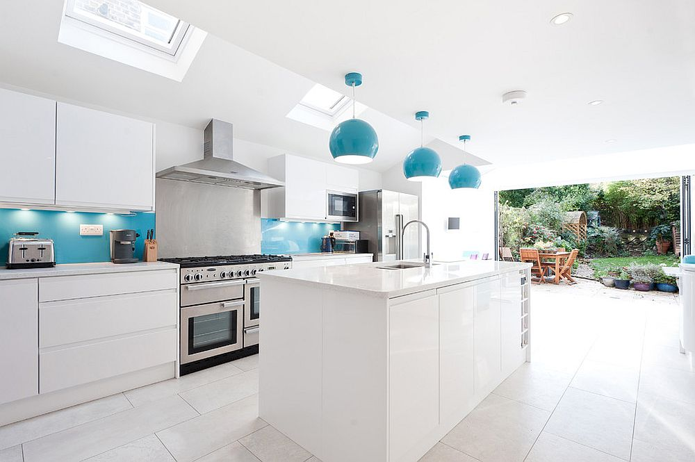 Stylish and urbane kitchen in white with blue backsplash and pendants