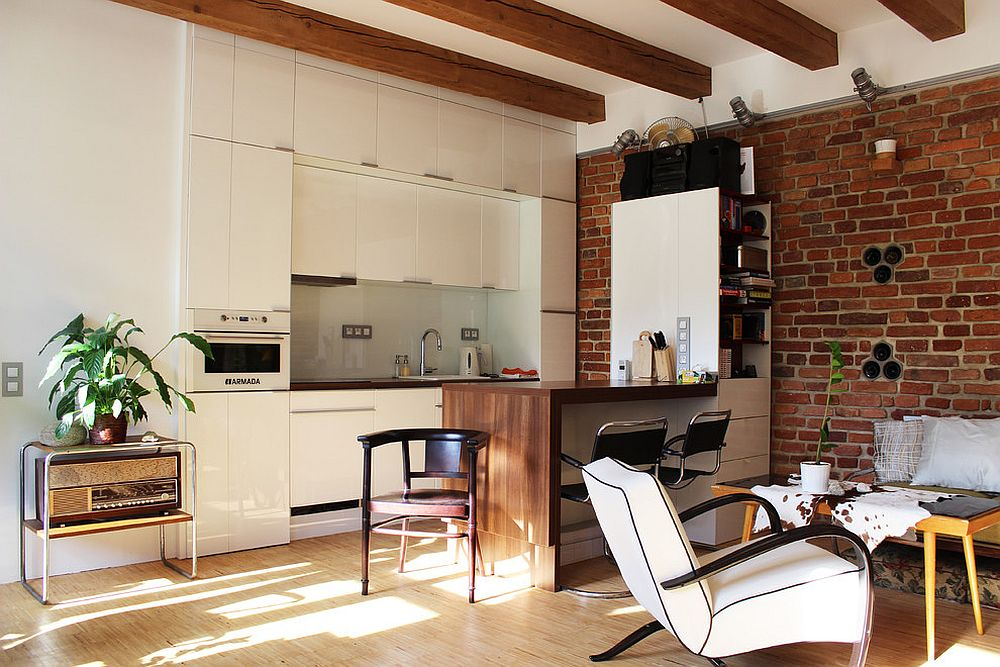 Tiny apartment kitchen in Prague combines white with brick wall charm