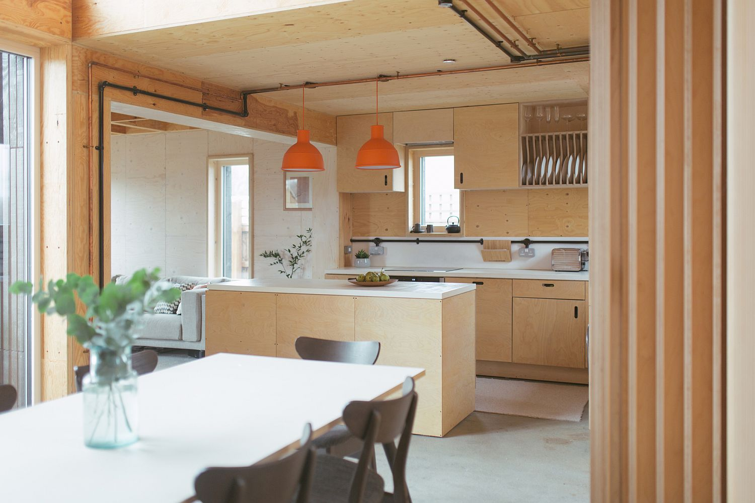 Twin-orange-pendants-add-color-to-the-neutral-kitchen-space