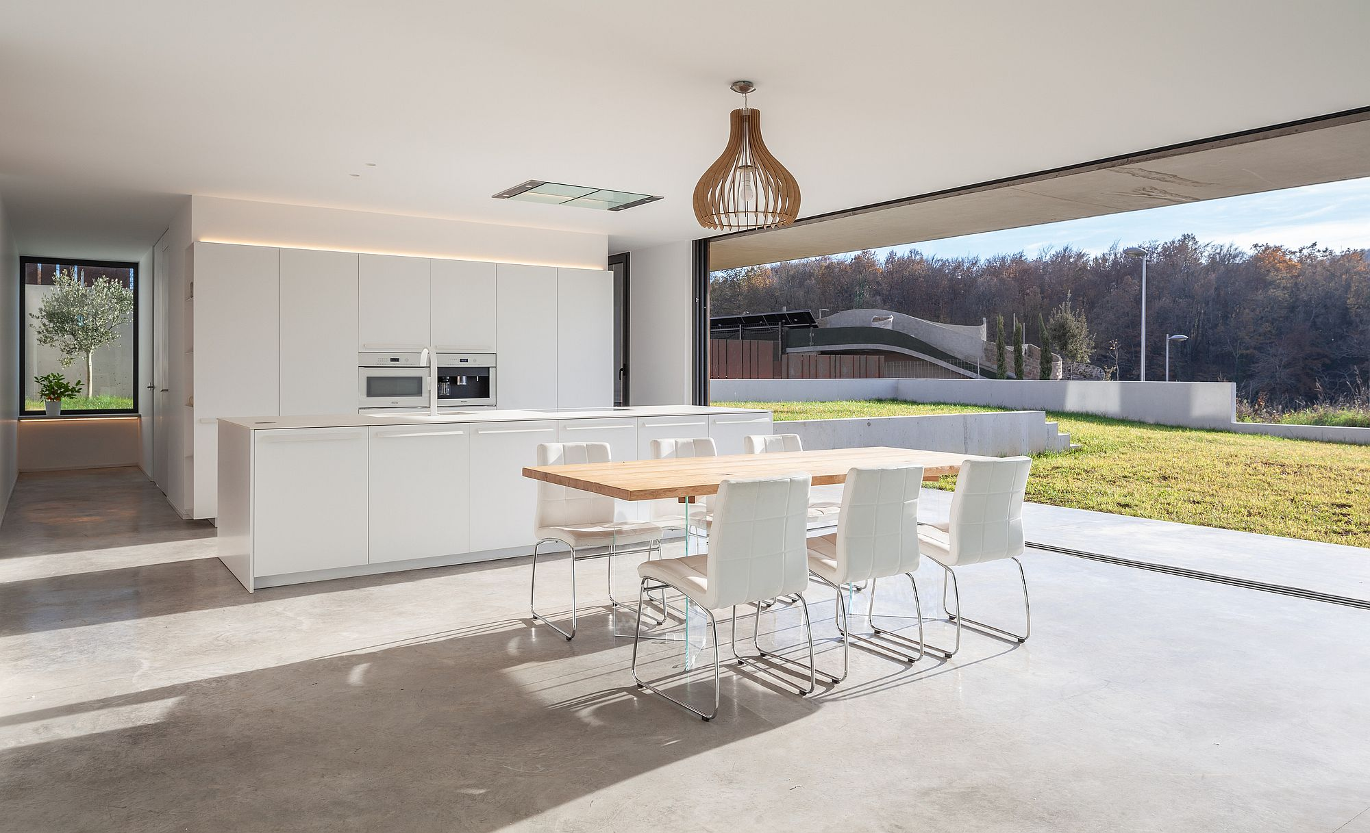 White and wood open kitchen design with concrete floor