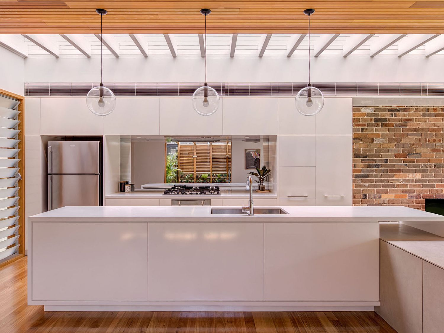 White, wood and brick kitchen of the contemporary home
