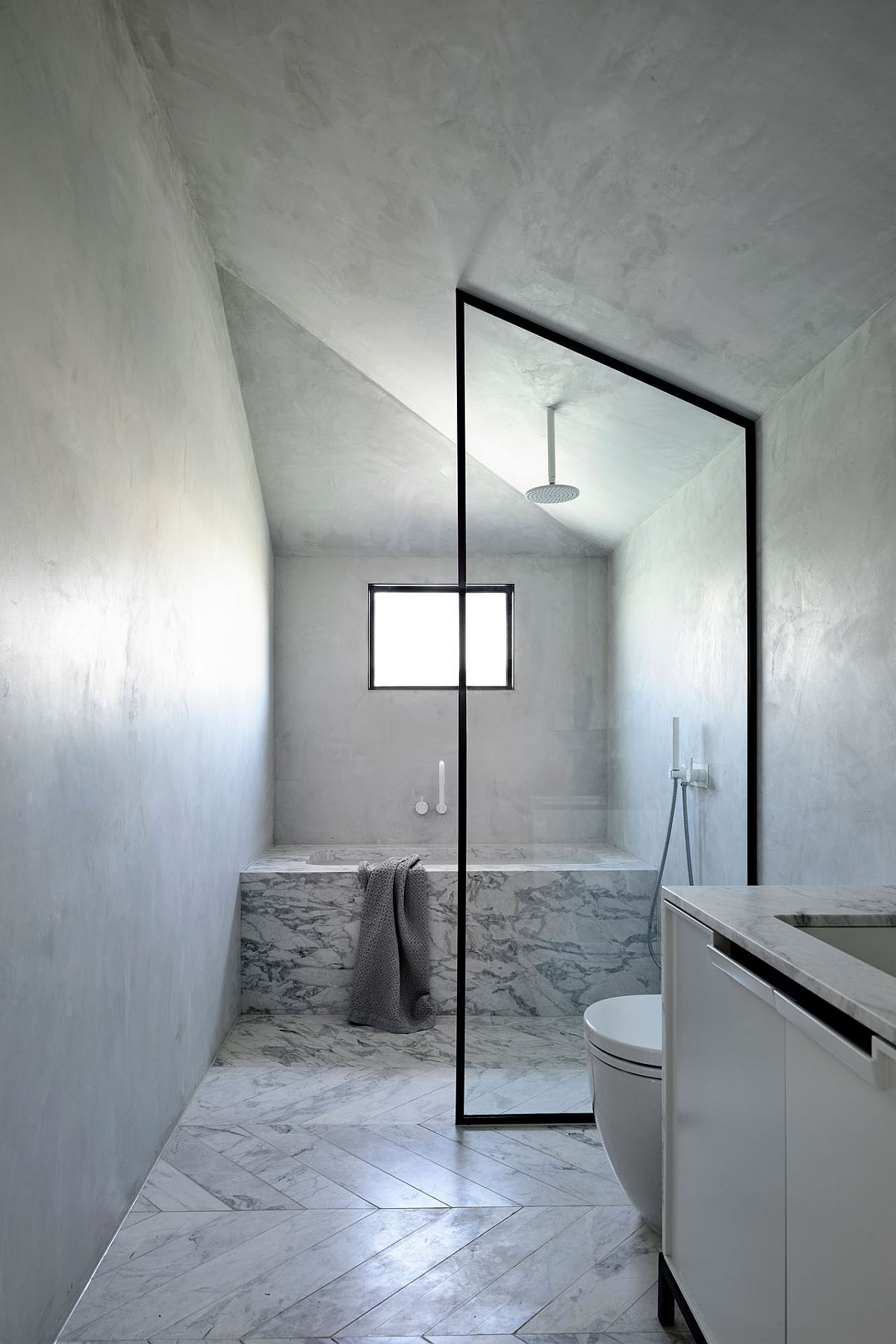Window in the corner brings light in the minimal white bathroom