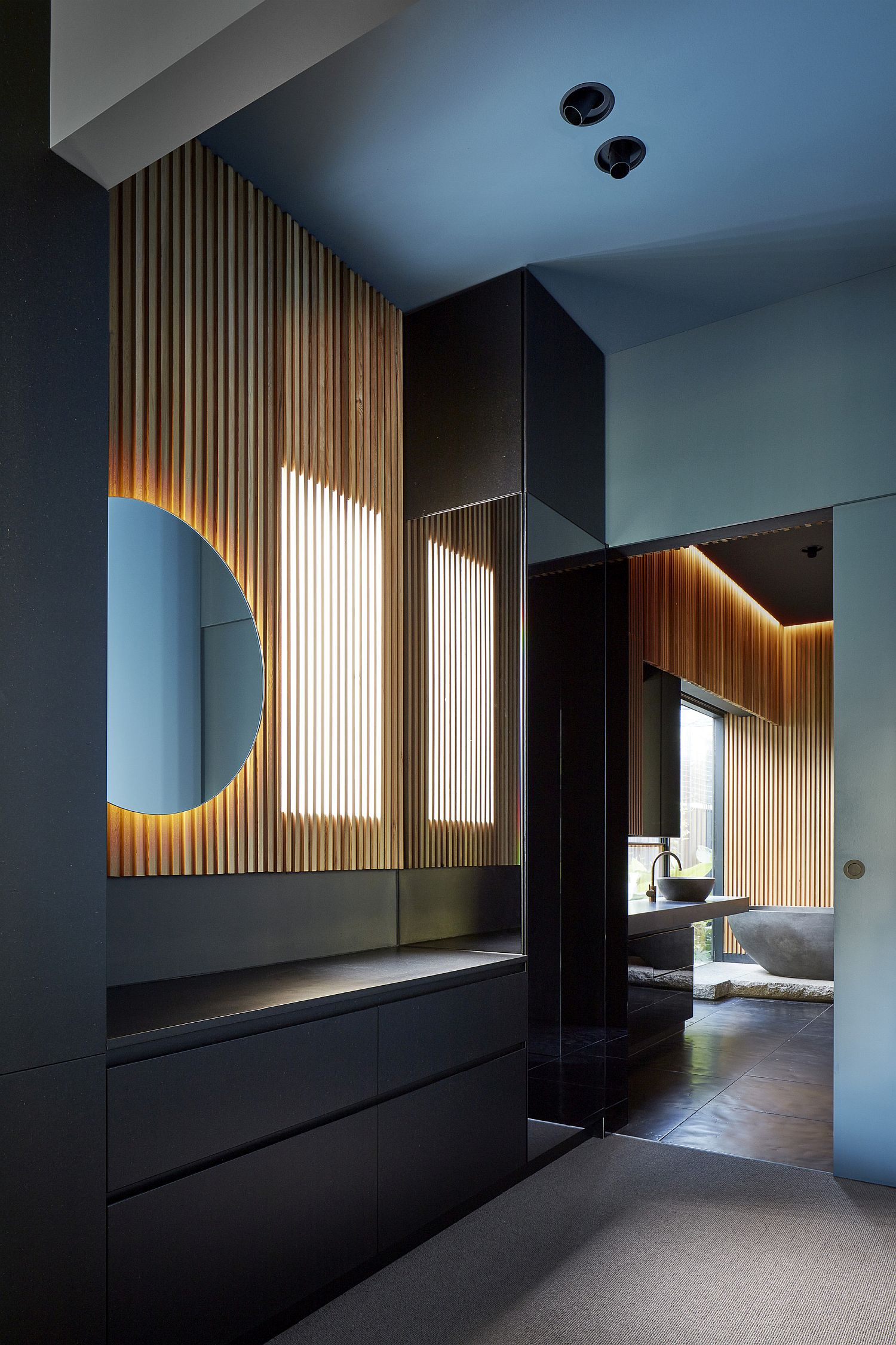 Wooden-slats-and-round-mirror-accentuated-by-brilliant-use-of-lighting