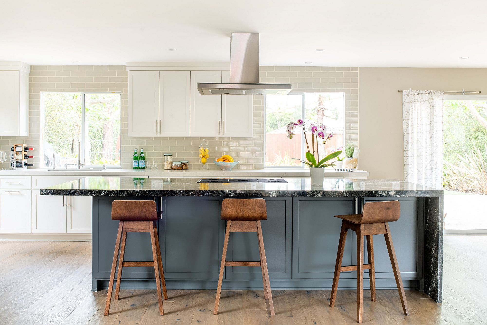 A touch of blue makes a big visual difference in the white kitchen with ample light