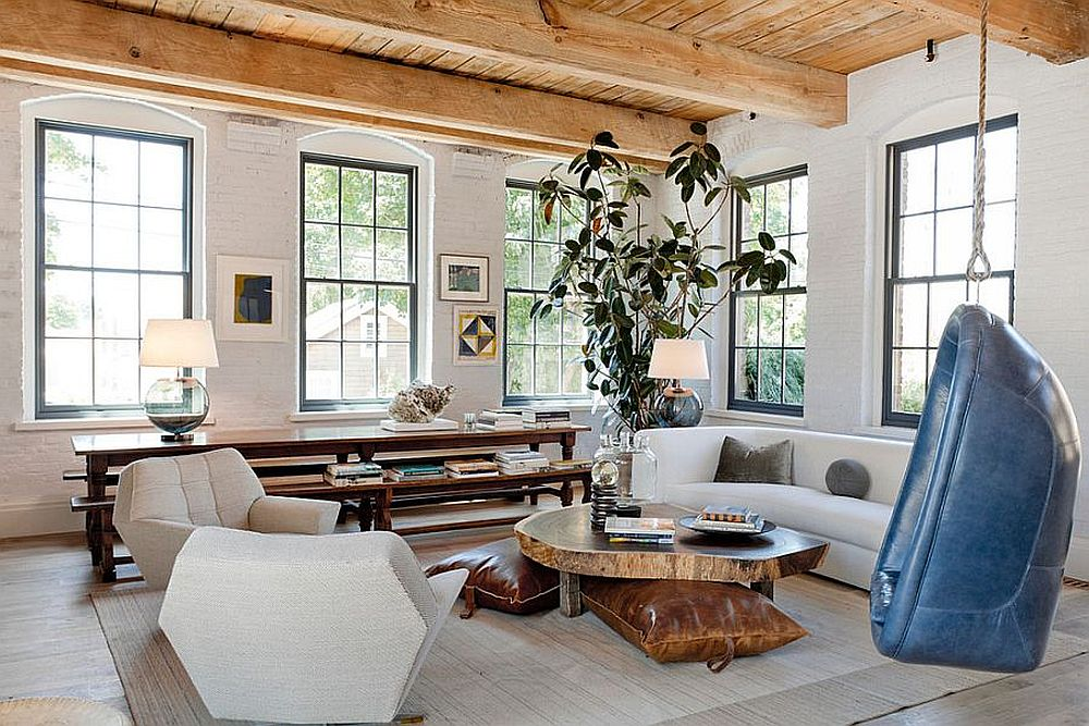 Brick wall painted in white along with natural woodsy ceiling of the living room add ample textural charm
