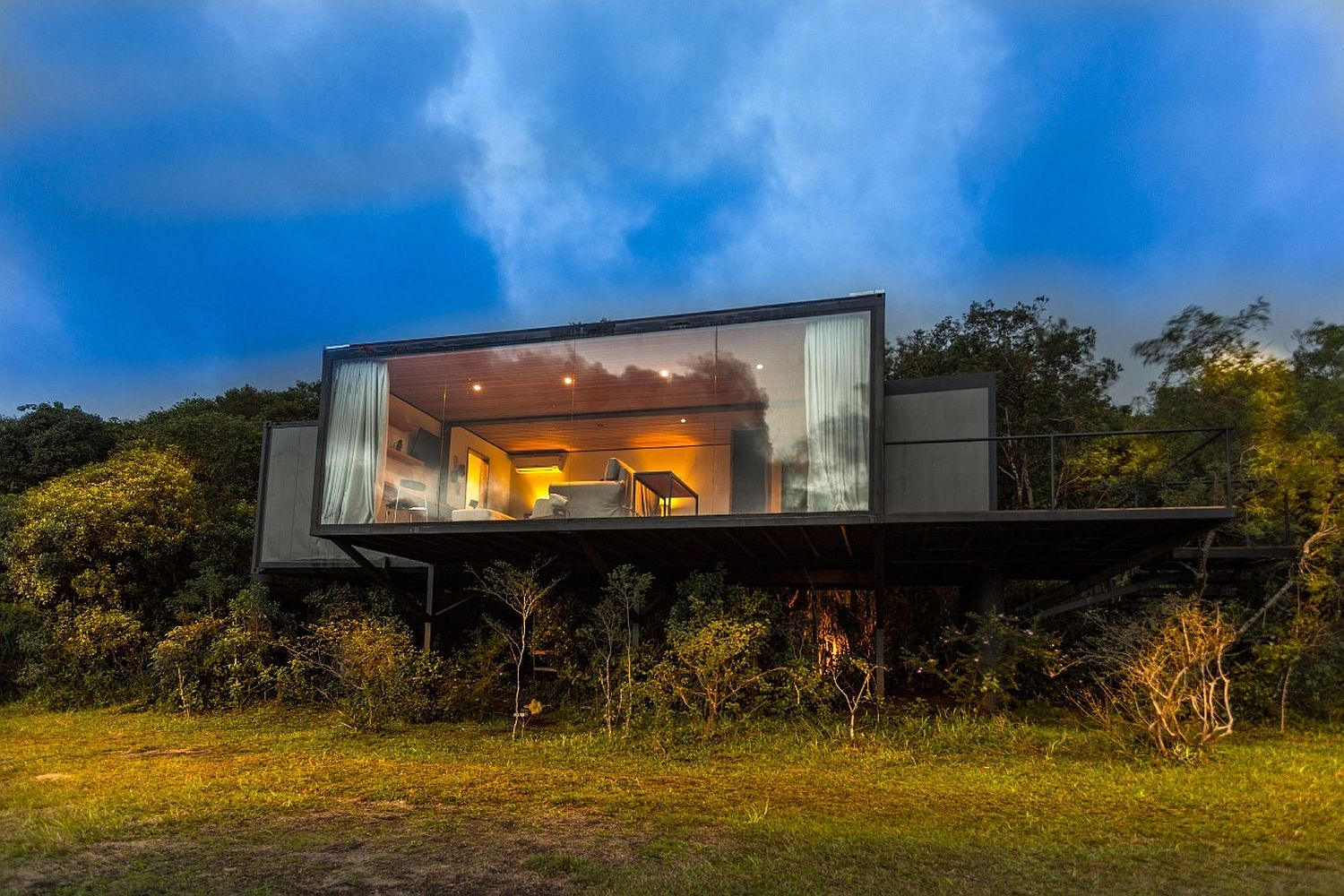 Elevated-design-o-the-cabin-overlooks-the-forest-and-green-landscape-outside