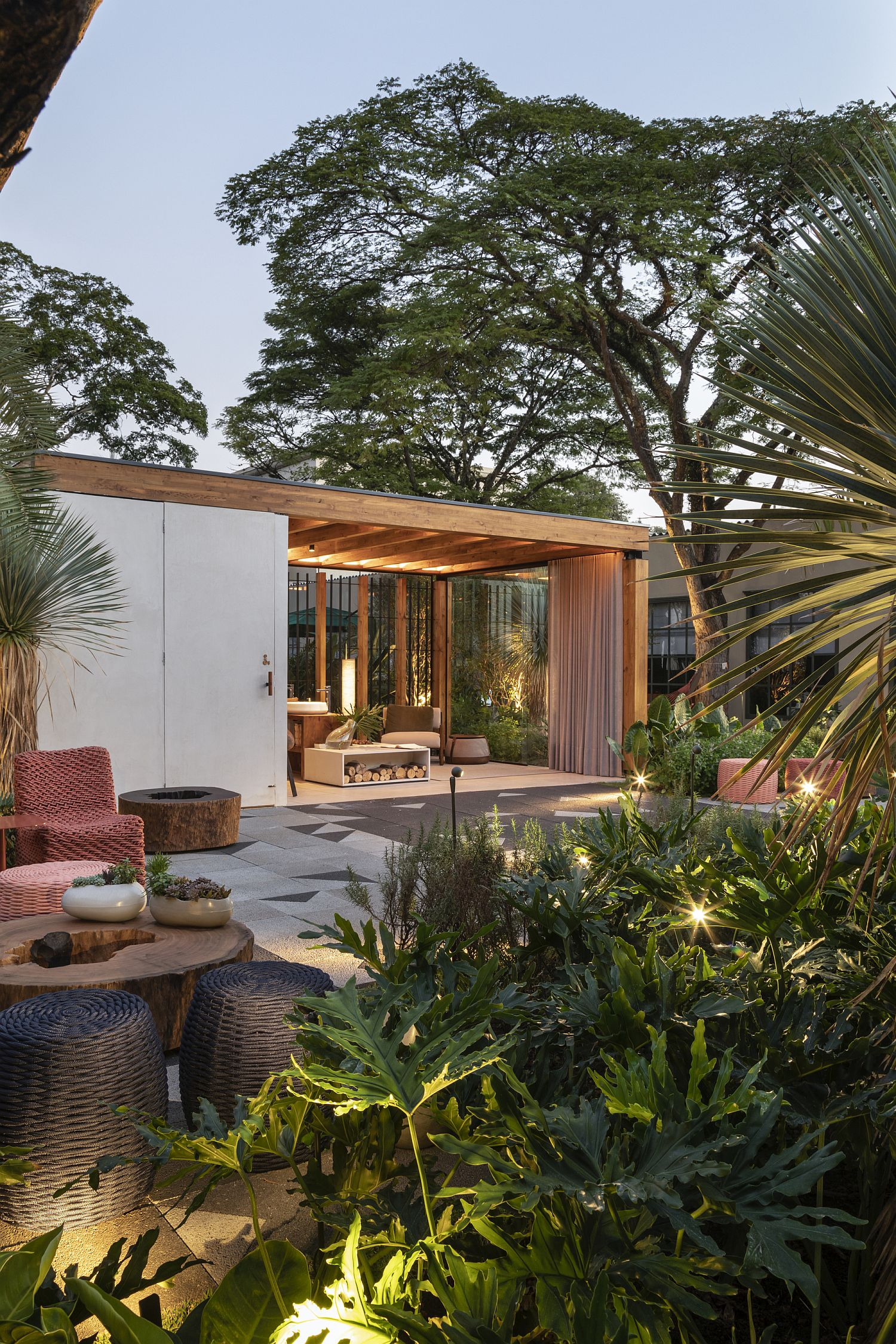 Greenery and lighting create a fabulous setting around the wooden terrace