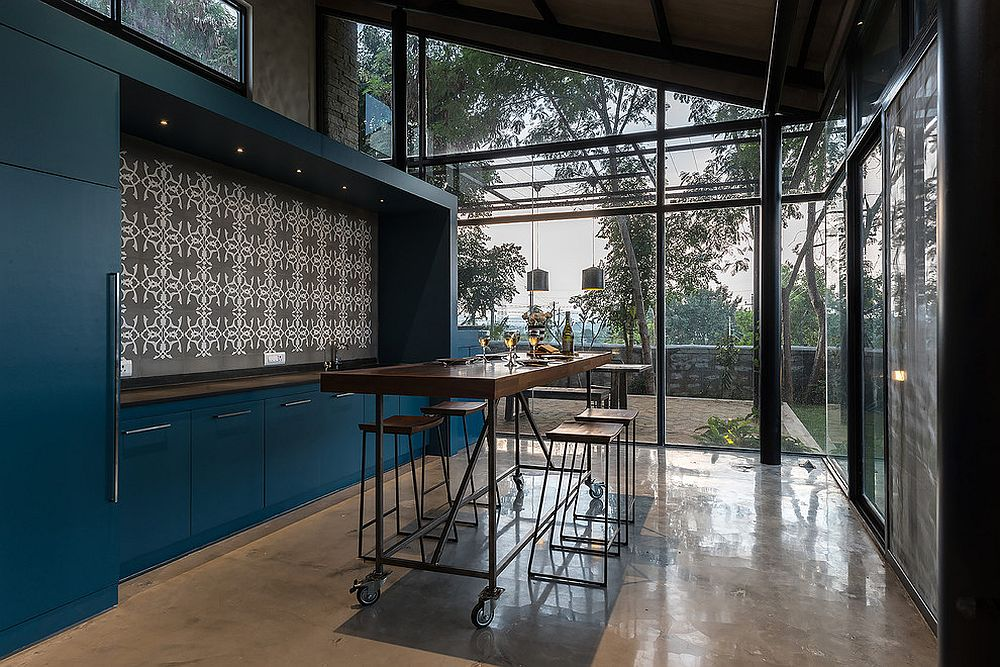 Island on wheels brings modualr charm to this industrial style kitchen with an overload of blue