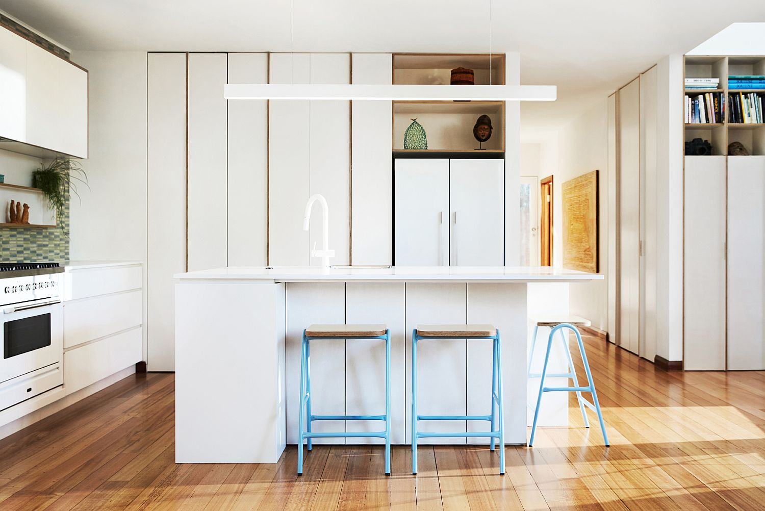It-is-the-bar-stools-that-add-pops-of-blue-to-this-exquisite-white-kitchen